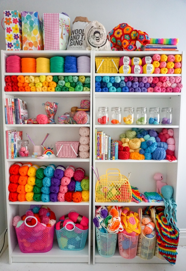 bookcase for yarn storage with crochet and craft supplies in rainbow colours
