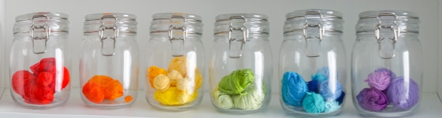 glass jam jars with small balls of yarn in rainbow colour order
