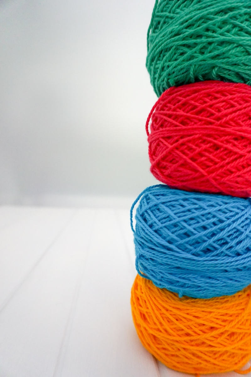 Stack of Cotton yarn in green, pink, blue and yellow