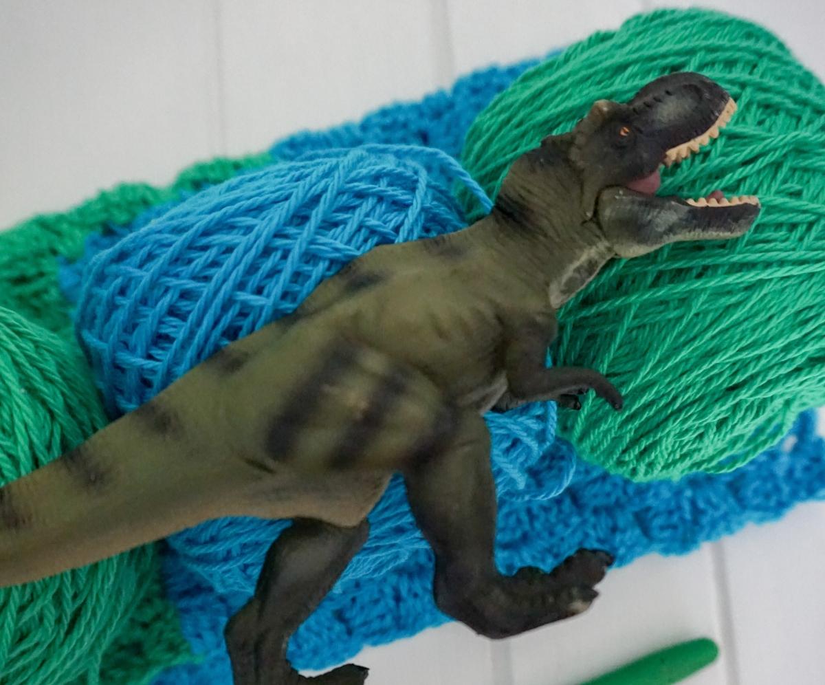 tyrannosaurus rex dinosaur figurine on blue & green yarn for crochet